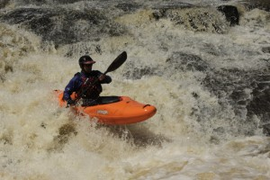 Roger Schumann kayaking a river rapid in Brazil.