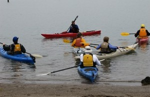 Six sea kayakers floating in the water during beginning kayak instruction.