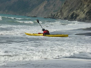 Yellow sea kayak launching into the surf during an intermediate kayak class