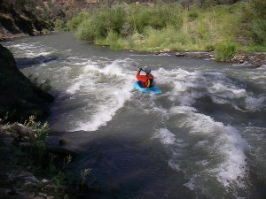 Blue kayak running a rapid.