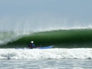 Sea Kayaker facing beautiful green wave.
