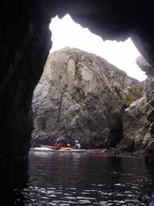Looking out a cave to two sea kayakers at Pt. Lobos.