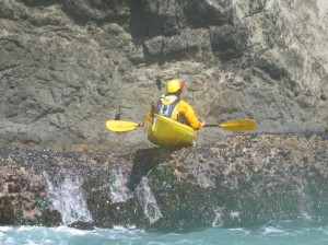 Sea kayaker resting on top of rocks waiting for the next surge.